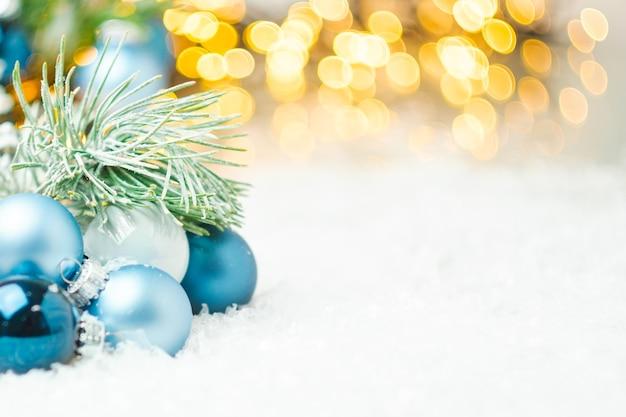 Blaue weihnachtskugeln und tannenzweig, die auf dem schnee auf dem hintergrund des weihnachtsbaumes liegen