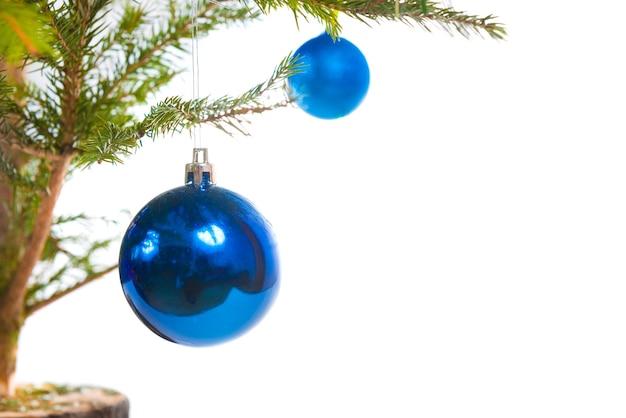 Blaue weihnachtskugeln und weihnachtsbaum isoliert auf weißem hintergrund