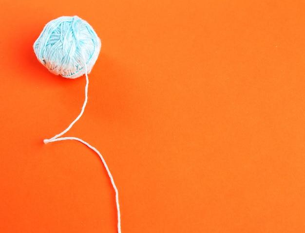 Blaue wollrolle auf orange