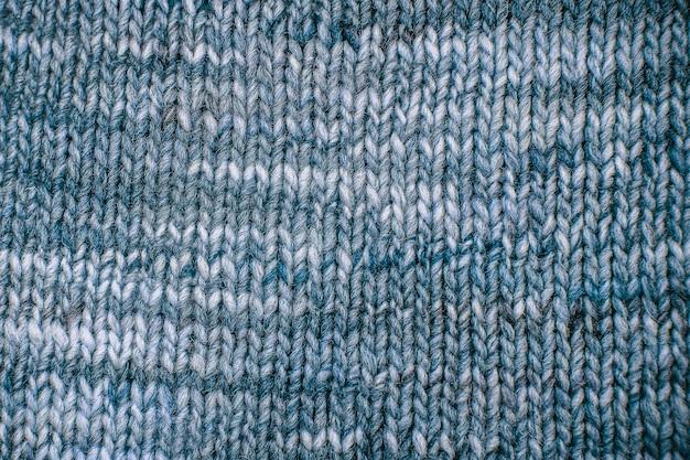 Blaue wollschalbeschaffenheit schließen oben. gestrickter jersey-hintergrund mit reliefmuster. zöpfe im maschinenstrickmuster