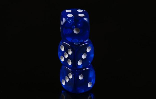 Blaue würfel auf einer schwarzen oberfläche. spielsucht. glück