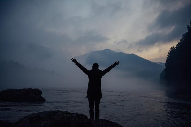 Blauer abendnebel über bergfluss auf dem hintergrund von bewaldeten hügeln und bedecktem himmel. mann steht im nebel, hände hoch und schaut auf die untergehende sonne. der appell der frau an die kraft der natur.