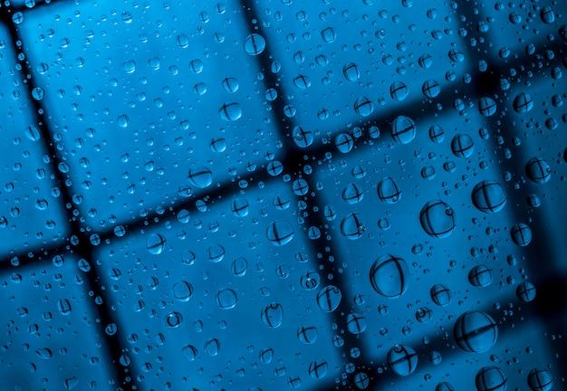 Blauer abstrakter unschärfehintergrund mit wassertropfen und reflexion auf transparentem glas. blauer hintergrund für einsames, trauriges und fehlendes jemand am regnerischen tageskonzept