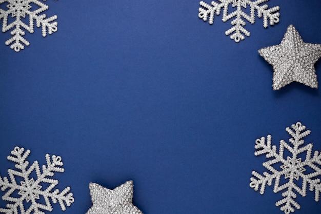 Blauer abstrakter weihnachtshintergrund mit silberner schneeflockenwinterdekoration, blauer spott oben mit raum für text.