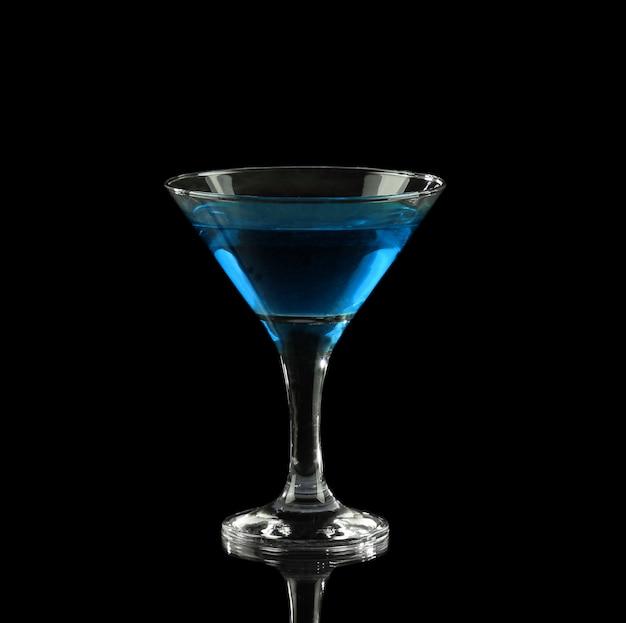 Blauer alkoholischer cocktail in einem glas auf schwarz