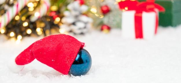 Blauer ball mit roter weihnachtsmannmütze auf dem schnee mit weihnachtsdekoration
