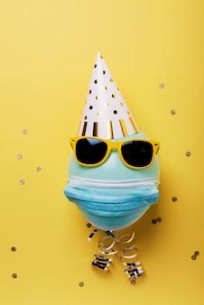 Blauer ballon mit schutzmaske, partyhut und sonnenbrille