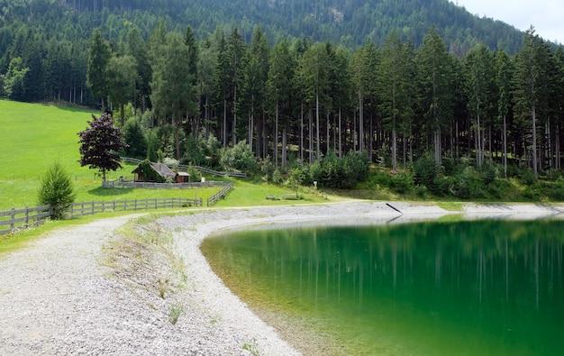 Blauer bergsee mit gras und bäumen bewölkt blauen himmel österreich