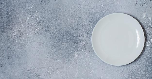 Blauer betonhintergrund für entwurf mit keramikplatte für lebensmittel. speicherplatz kopieren.