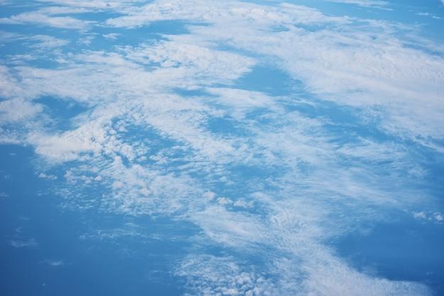 Blauer bewölkter himmel, blick vom flugzeugfenster. luftaufnahme der wolkenlandschaft