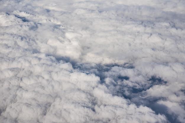 Blauer bewölkter himmel, blick vom flugzeugfenster. luftaufnahme der wolkenlandschaft.
