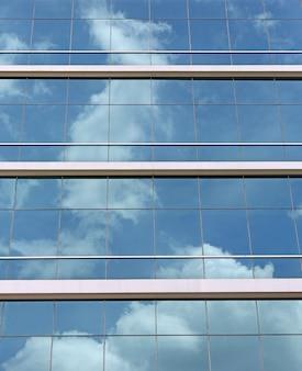 Blauer bewölkter himmel reflektierte sich in einer glaswand