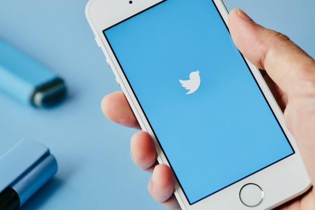 Blauer bildschirm der twitter-app, unscharfer blauer markierungsstift als hintergrund