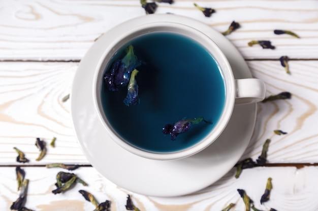 Blauer blumentee der schmetterlingserbse in einer weißen schale. gesundes detox-kräutergetränk. blauer tee anchan der schmetterlingserbsen in einer draufsicht der schale
