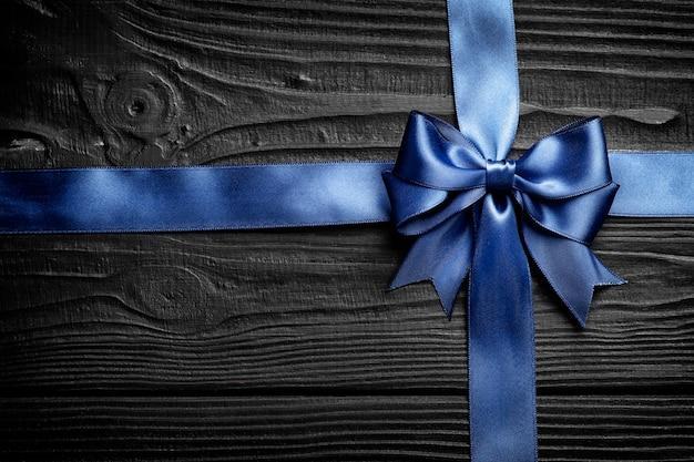 Blauer bogen und band des schönen geschenks auf einem schwarzen hölzernen hintergrund. herzlichen glückwunsch konzept.