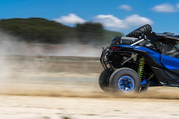 Blauer buggy-rennen auf feldweg - extremsport
