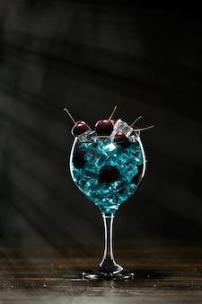 Blauer cocktail in einem glas mit eis und kirschen