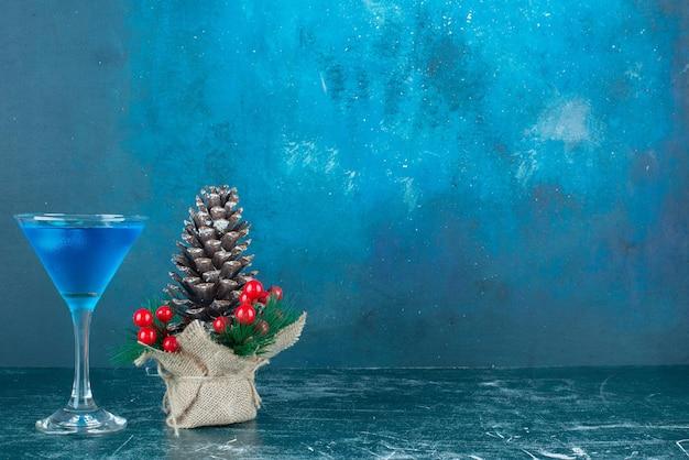 Blauer cocktail in einem glas neben weihnachtsschmuck auf marmor.