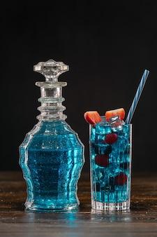 Blauer cocktail in vintage-karaffe und in einem glas auf holztisch
