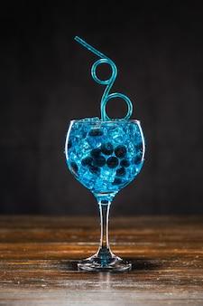 Blauer cocktail mit blaubeere und eis in einem glas auf holztisch