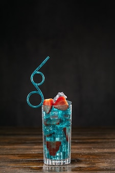 Blauer cocktail mit eis und erdbeeren