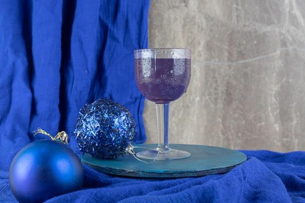 Blauer cocktail mit glitzernden kugeln auf blauem teller