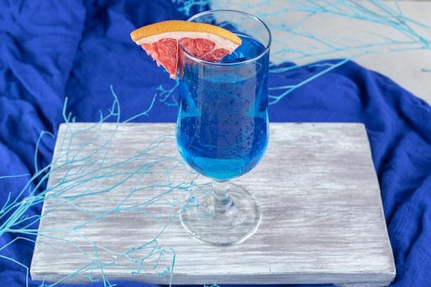 Blauer cocktail mit grapefruitscheibe auf holzbrett