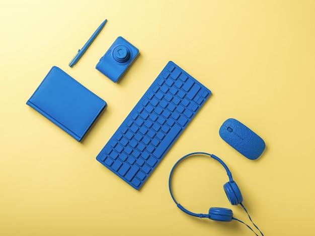 Blauer computer und schreibwarenzubehör auf gelbem hintergrund. stilvolles zubehör für geschäftsreisende und freiberufler. flach liegen.