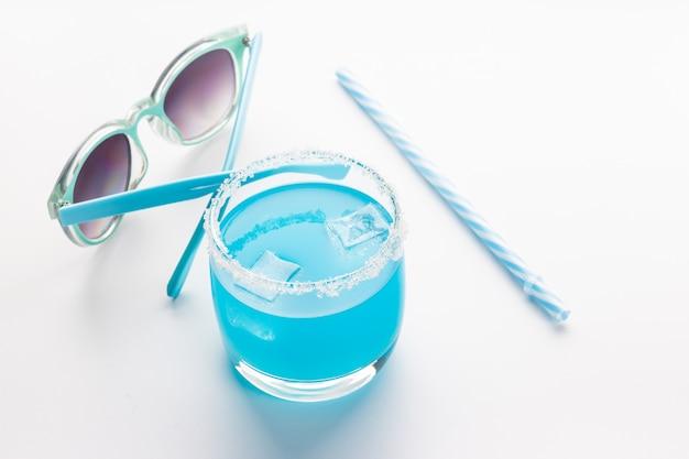 Blauer curaçao-cocktail und sonnenbrille auf dem tisch