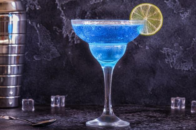 Blauer curaçao-cocktail, verziert mit früchten