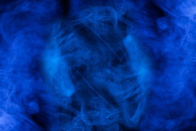 Blauer dampf auf schwarzem hintergrund. platz kopieren.