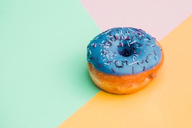 Blauer donut auf farbigem hintergrund