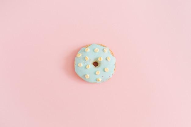Blauer donut auf pastellrosa hintergrund