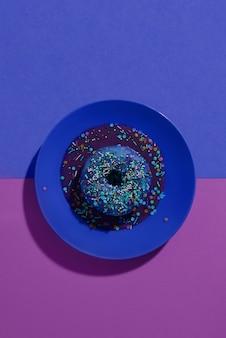 Blauer donut mit purpurroter verglasung und mehrfarbigem pulver auf einem blauen teller.
