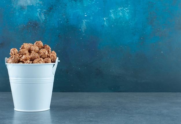 Blauer eimer mit knusprigen und würzigen popcorn-süßigkeiten auf blauem hintergrund. foto in hoher qualität