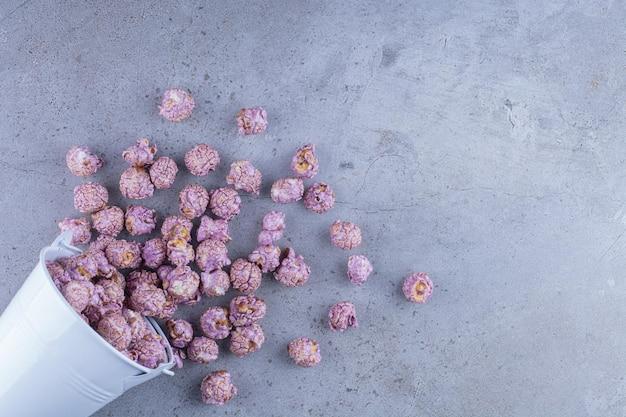 Blauer eimer mit popcornbonbons, die auf marmoroberfläche übergelaufen sind