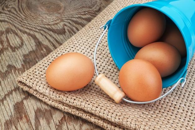 Blauer eimer und ostereier verstreut auf sackleinen.