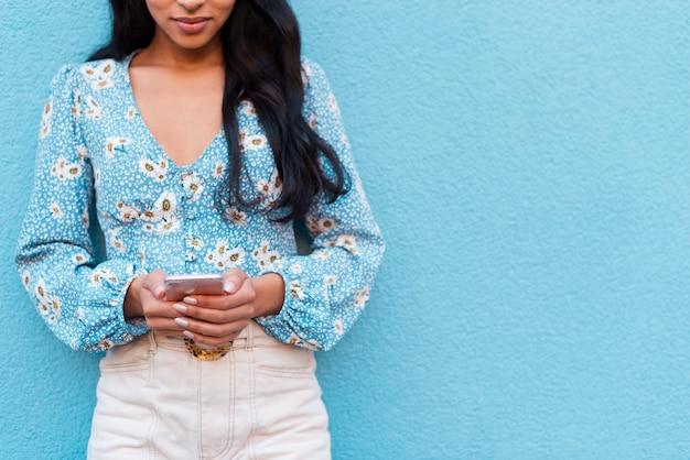 Blauer exemplarplatzhintergrund und -frau mit telefon