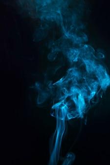 Blauer farbraucheffekt auf dem schwarzen hintergrund