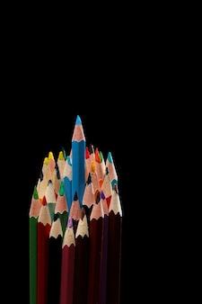 Blauer farbstift sticht unter vielen farbstiften auf schwarzem hintergrund hervor