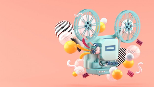Blauer filmprojektor inmitten bunter kugeln auf rosa. 3d rendern.