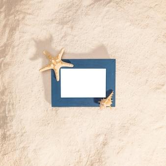 Blauer fotorahmen mit getrocknetem stern auf strand