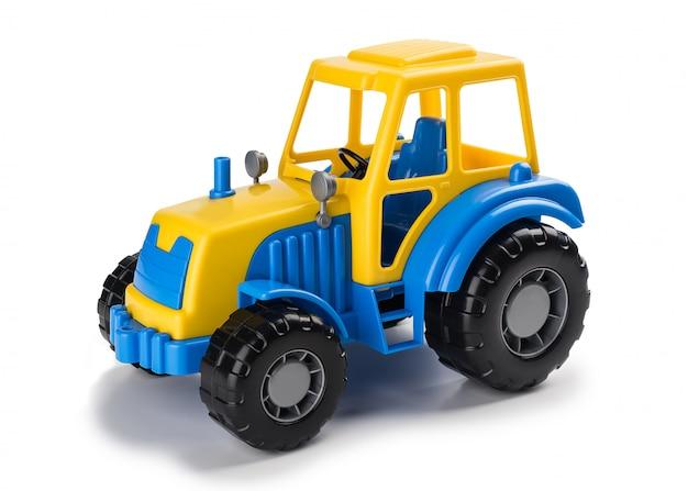 Blauer gelber traktor des spielzeugs der kinder auf einem weiß lokalisierten hintergrund.