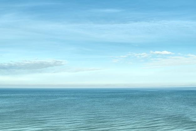 Blauer heller himmel und seehintergrund am sonnigen tag
