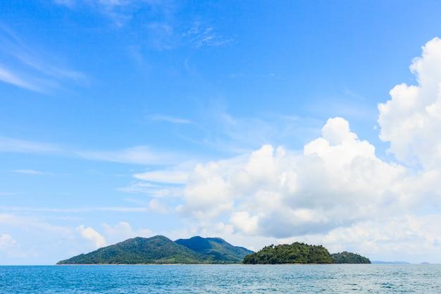 Blauer himmel des schönen sommers über tropischem ozean und insel