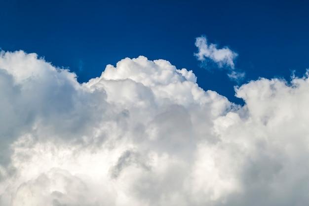 Blauer himmel mit geschwollenen weißen wolken am hellen klaren sonnigen tag