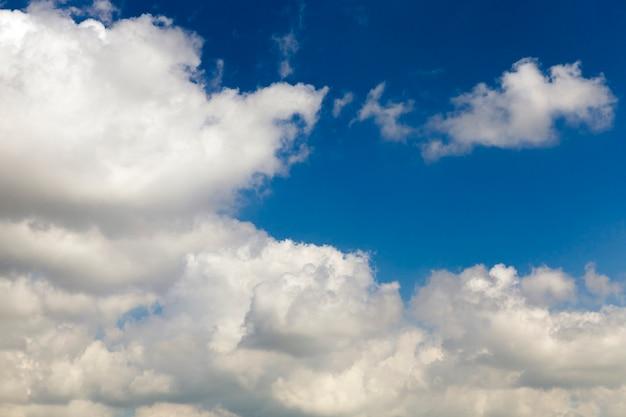 Blauer himmel mit weißen cumuluswolken in der frühlingssaison.