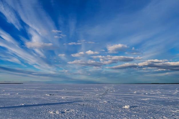 Blauer himmel mit wolken an einem wintertag über dem eis des flusses