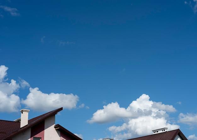 Blauer himmel und weiße wolken über dem dreieckigen dach eines hauses der himmel ist morgens oft blau