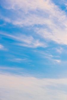 Blauer himmel und weißer wolkenhintergrund am sonnigen tag.